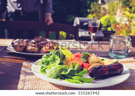 Salad, sausage and chicken at family barbecue