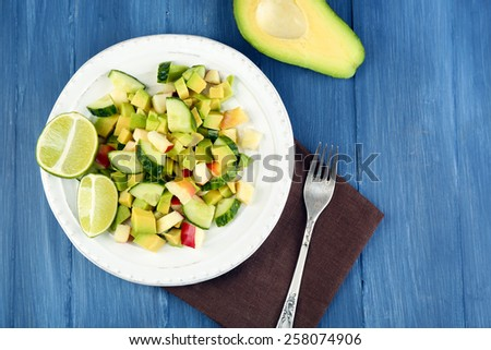 Salad with apple and avocado in bowl on table close up - stock photo