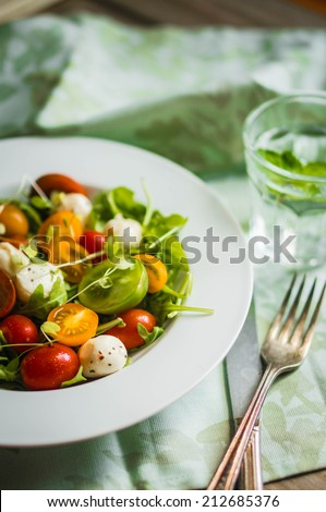 Salad with arugula,tomatoes and mozarella on wooden background