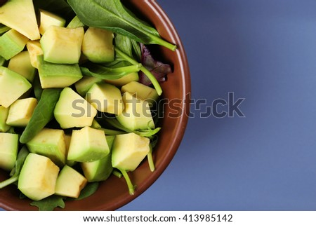 Salad with avocado and sorrel in bowl on grey background, top view - stock photo