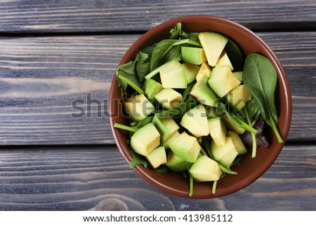Salad with avocado and sorrel in bowl on wooden background, top view - stock photo