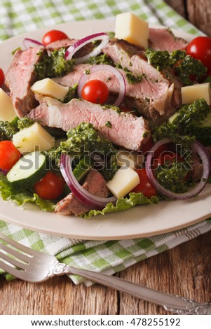 Salad with beef steak, cheese and fresh vegetables dressed with chimichurri sauce closeup on a plate. vertical