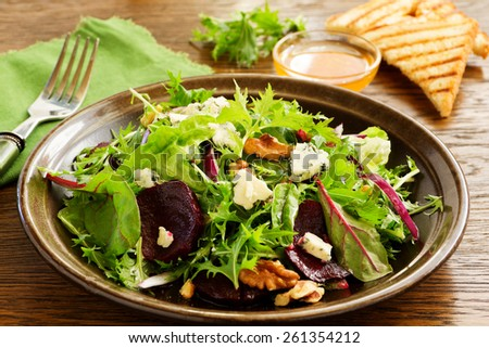 Salad with beets, blue cheese, walnuts with vinaigrette - stock photo