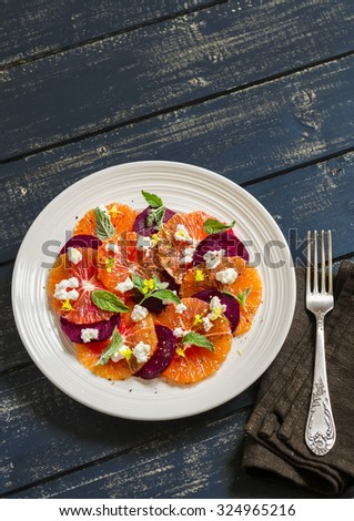 salad with beets, oranges and soft cheese on a white plate on a dark wooden background - stock photo