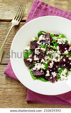salad with beets, spinach and goat cheese on a dark wood background. tinting. selective focus on the middle of the salad - stock photo