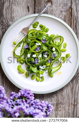 Salad with broad beans, asparagus and lilac - stock photo