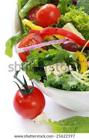 Salad with cherry tomatoes, goat's cheese, peppers, lettuce, onion and black olives.  Delicious healthy eating. - stock photo