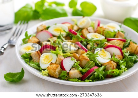 Salad with chicken, croutons, radish and quail eggs on white background - stock photo