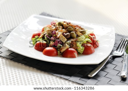 salad with chicken, tomatoes and olives on table set