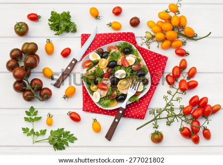 Salad with chicken, tomatoes, olives, lettuce, quail eggs and olive oil on a white wooden table with variety of tomatoes, top view - stock photo
