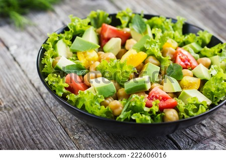 Salad with chickpeas, tomato and avocado - stock photo