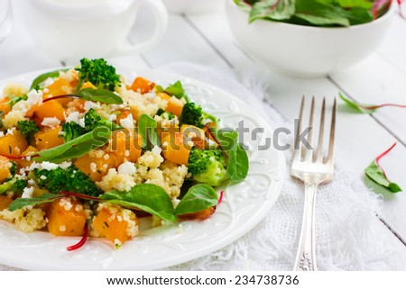 Salad with couscous, pumpkin, broccoli and feta - stock photo