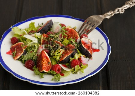 Salad with figs and raspberries, dressed with raspberry sauce and Parmesan cheese.selective focus - stock photo