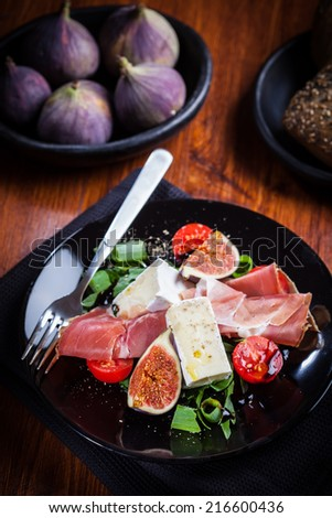 Salad with fresh figs, cheese, prosciutto and cheese - stock photo