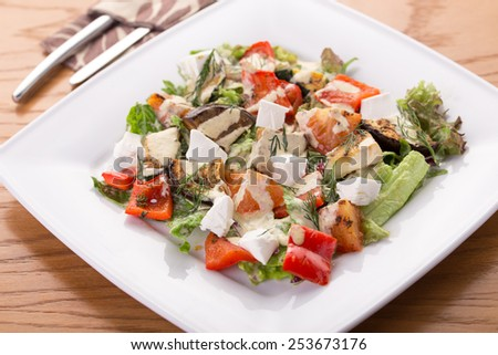 Salad with fresh, grilled vegetables and cheese on wooden table - stock photo