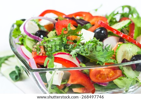 Salad with fresh vegetables and herbs in a glass bowl - stock photo