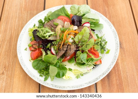 Salad with fried rabbit liver and fresh vegetables on a wooden table.