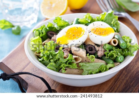 Salad with greens, pasta, tuna and boiled egg - stock photo