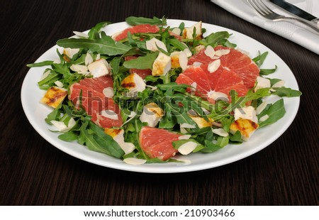 Salad with grilled chicken and arugula, grapefruit, almonds - stock photo