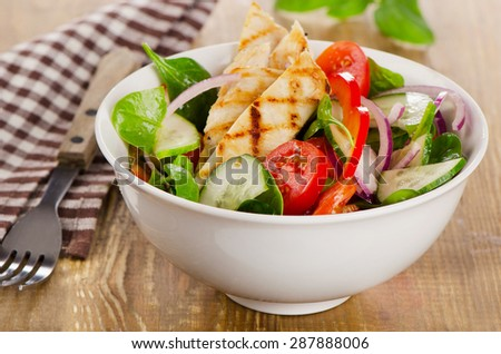 Salad with grilled chicken in  white bowl. Selective focus - stock photo