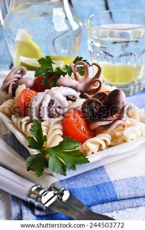 Salad with octopus, pasta and tomato on a ceramic plate