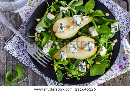 salad with pears, arugula, blue cheese and pine nuts on a black plate, top view - stock photo