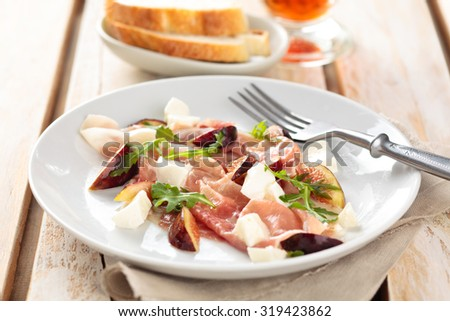 Salad with prosciutto, figs, parmesan cheese and arugula. - stock photo