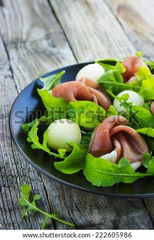 salad with prosciutto, melon and arugula - stock photo