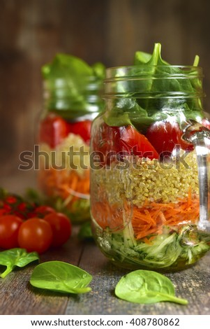 Salad with quinoa and vegetables in a mason jar on a rustic wooden background. - stock photo