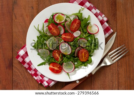salad with radish on plate on brown background - stock photo