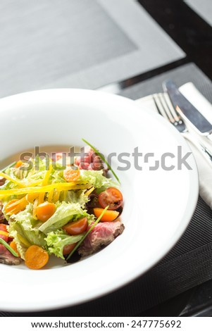 Salad with roast beef and vegetables isolated on black table - stock photo