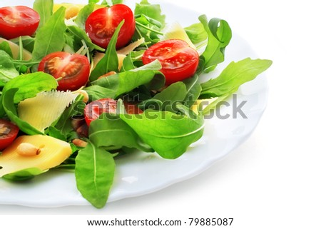 Salad with ruccola, pine nuts, cheese and baby tomatoes on white background.