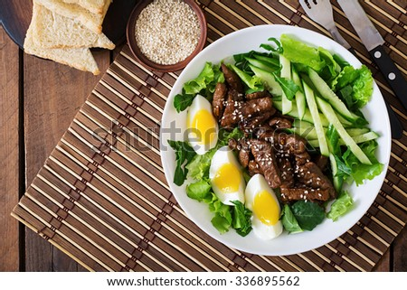 Salad with spicy beef, cucumber and eggs in the Asian style. Top view - stock photo