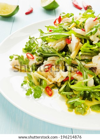 Salad with steamed sea bass fillet, chili pepper, rucola, cilantro and ginger in olive and linseed oil. Shallow dof.