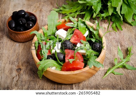 Salad with tomatoes and olives on wooden background. a bowl of salad and a bunch of arugula, a bowl of olives behind - stock photo
