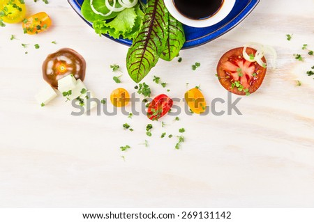 Salad with tomatoes, feta cheese and balsamic vinegar in blue plate on white wooden background, top view frame - stock photo