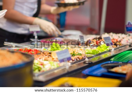 Salads and other dishes with vegetables and meat on table in restaurant
