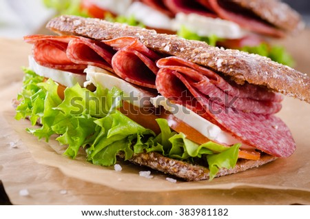 Salami and brie sandwiches with fullcorn bread on white wooden background