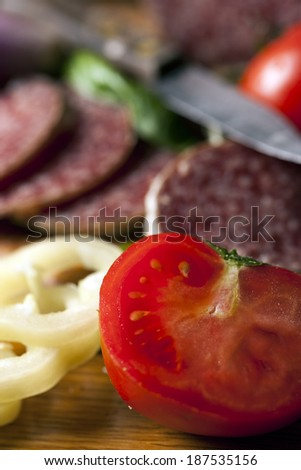 Salami and vegetables on wooden desk