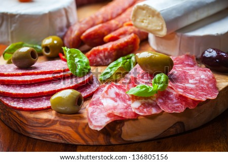 Salami catering platter with different meat and cheese products - stock photo