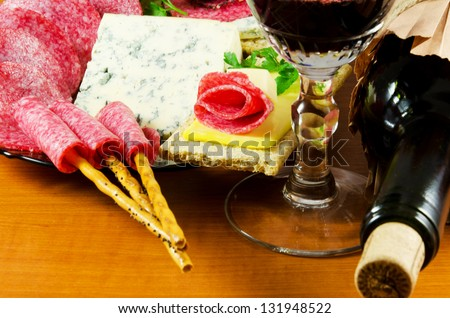 Salami ,cheese and red wine on a wooden table - stock photo