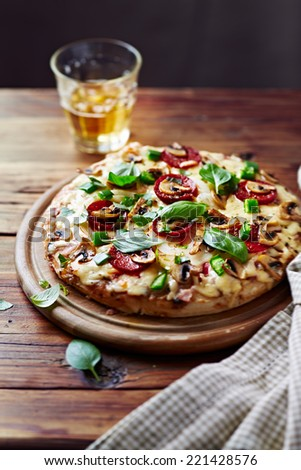 Salami Pizza with Mushrooms and a Glass of Beer - stock photo