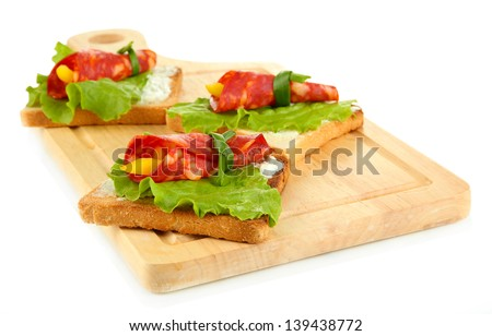 Salami rolls with paprika pieces inside, on  roasted bread, on wooden board, isolated on white
