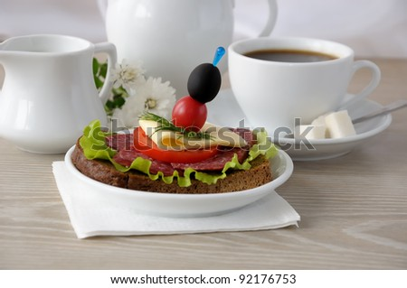 Salami sandwich and a cup of coffee with milk in the milkman - stock photo