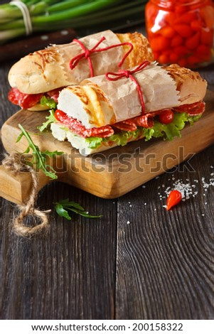 Salami sandwiches with lettuce and sweety drop peppers on an old wooden board with place for text. - stock photo
