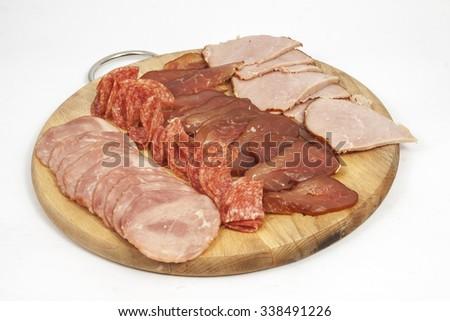 Salami sausage slicesand ham on a wooden board - stock photo
