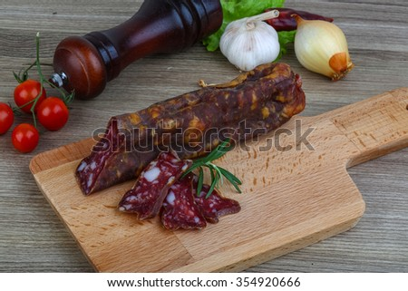 Salami sausage with rosemary on the wood background