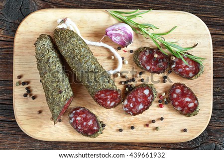 Salami sausages sliced with spices on cutting board, top view
