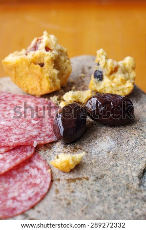 Salami slices, Greek olives and the broken cake on a stone