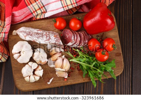 Salami with cherry tomatoes, pepper, garlic and arugula on a cutting board on wooden table